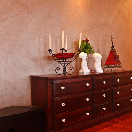 Holzkommode, darauf Büsten und ein Kerzenständer