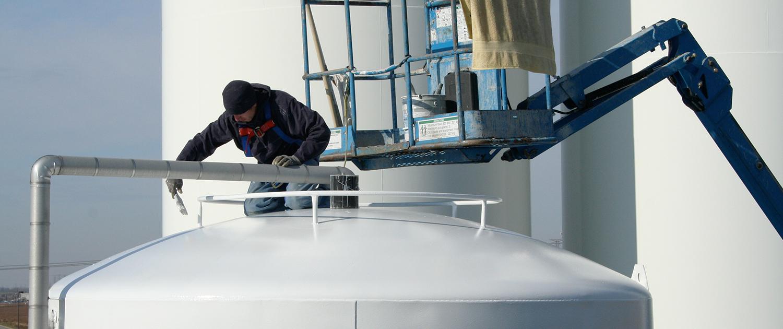 Ein Industriemaler bei der Arbeit auf einem großen Kessel