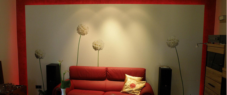 Ein rotes Sofa vor einer mit weißen Blumen tapezierten Wand