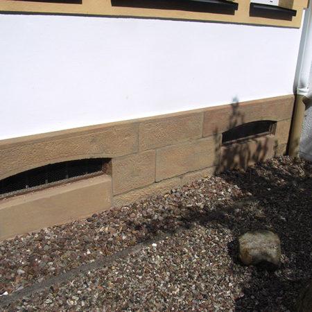 Renovierte Fassadensteine an einem Kellerfenster